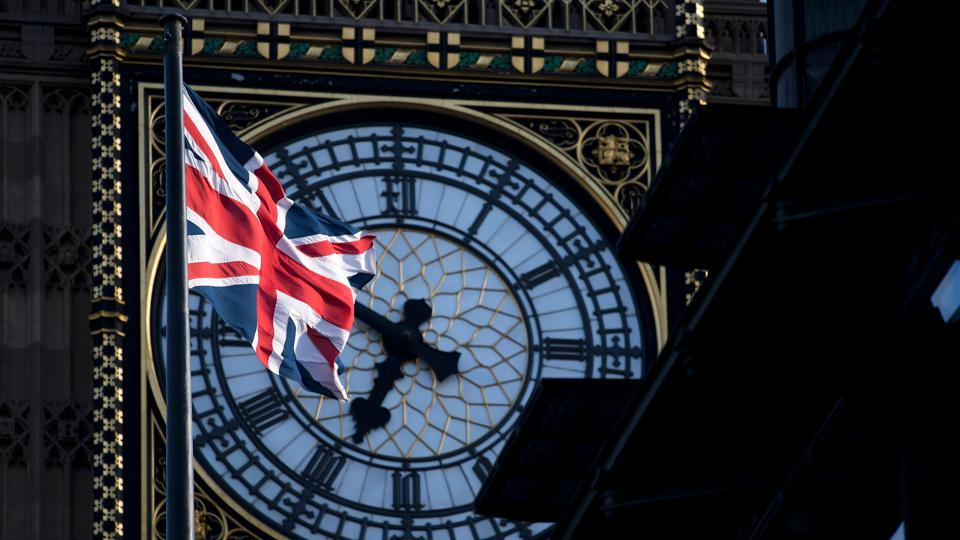 A Union flag flies in the wind in front of the clock face of Elizabeth Tower, commonly referred to as Big Ben, near the Houses of Parliament in Westminster.