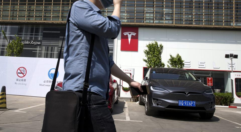 A man wears a mask walks past a Tesla electric vehicle showroom and charging station in Beijing, China.