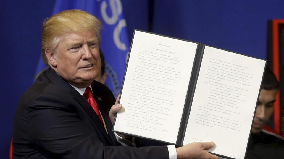 President Donald Trump holds up an executive order to tighten the rules for technology companies seeking to bring highly skilled foreign workers to the US, before signing, on Tuesday.