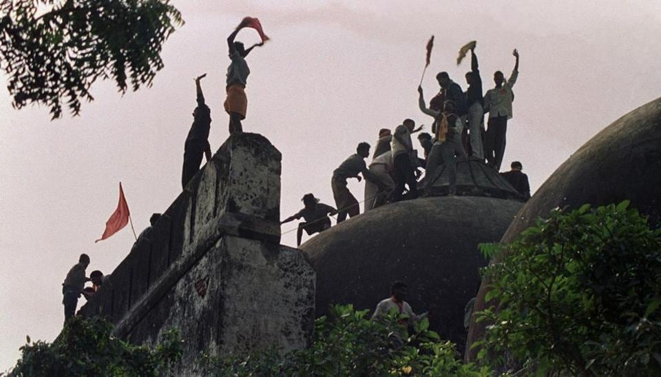 This file photo taken on December 6, 1992 shows Hindu fundamentalists shouting and waving banners as they stand on top of a stone wall and celebrate the destruction of the 16th century Babri Mosque in Ayodhya.