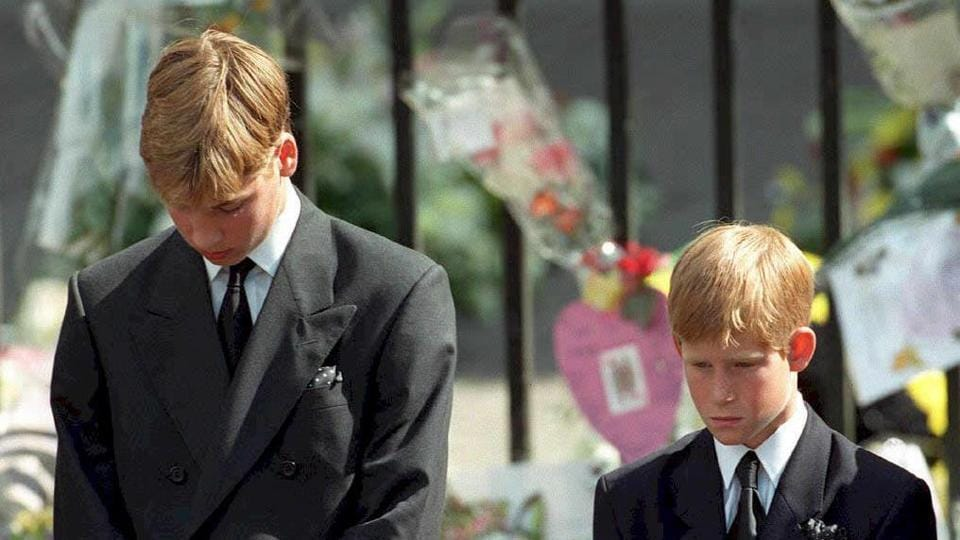 Photo taken on September 06, 1997 shows Britain's Prince William (L) and Prince Harry (R) bowing their heads as their mother Prince Diana's coffin is taken out of Westminster Abbey following her funeral service.