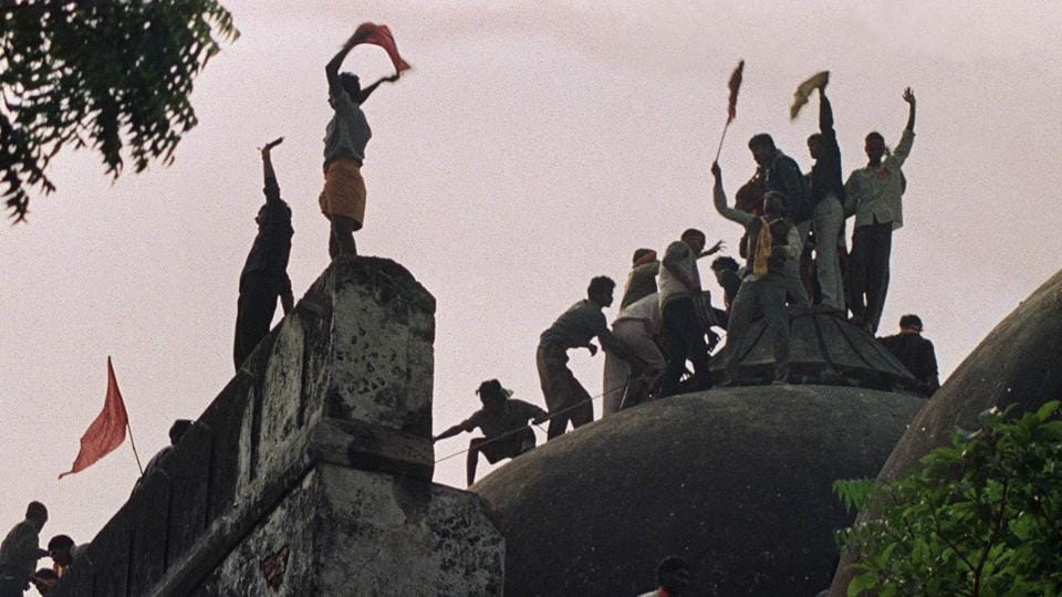 This photo taken on December 6, 1992, shows a Hindu mob shouting and waving banners as they stand on the top of a stone wall and celebrate the destruction of the 16th Century Babri mosque in Ayodhya.