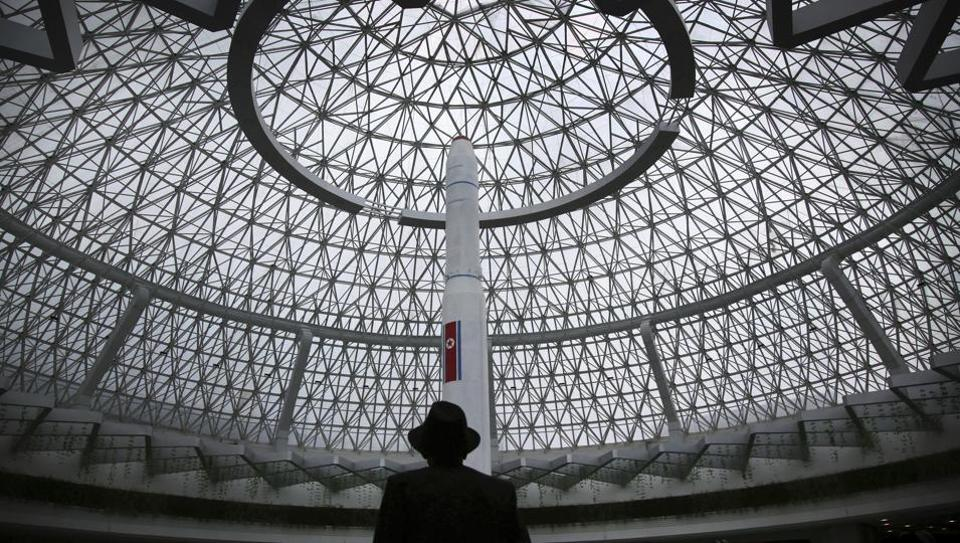 An elderly North Korean man is silhouetted against a model of the Unha 3, a space launch vehicle, displayed at the Sci-Tech Complex in Pyongyang, North Korea.