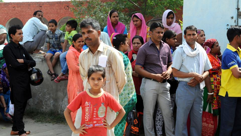 Parents of students who applied under EWS quota wait for the list outside the office of the block elementary education officer in Gurgaon.