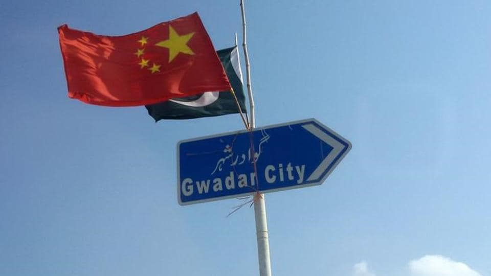 The Chinese and Pakistani flags fly on a sign along a road towards Gwadar, Pakistan.