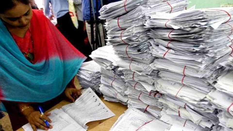 Tax officials scrutinising a tax return form in New Delhi.