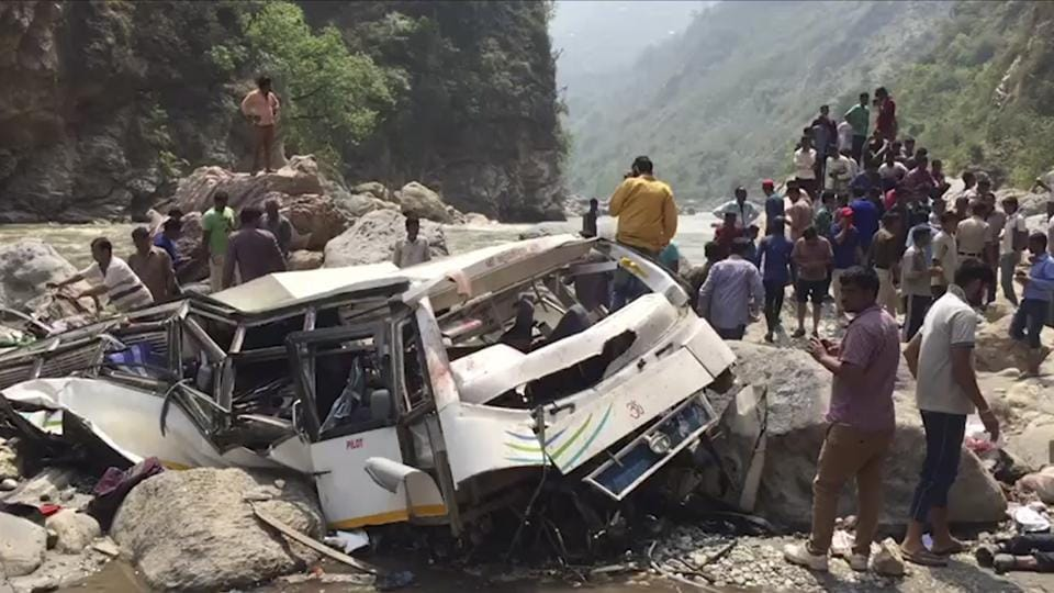 People stand near the wreckage after a passenger bus swerved off a mountain road and plunged into a gorge on the Tons river in Himachal Pradesh.