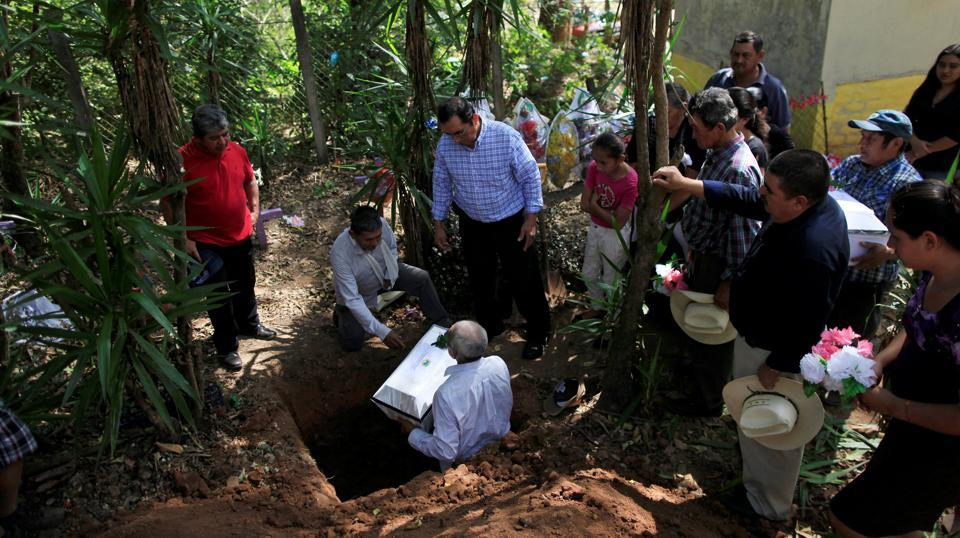 Relatives participate in the funeral of Petrona Chavarria and Vilma Ramos, who died in the El Mozote massacre. In 1991, Argentine forensic experts began helping to disinter remains to identify the victims (Jose Cabezas  / Reuters)