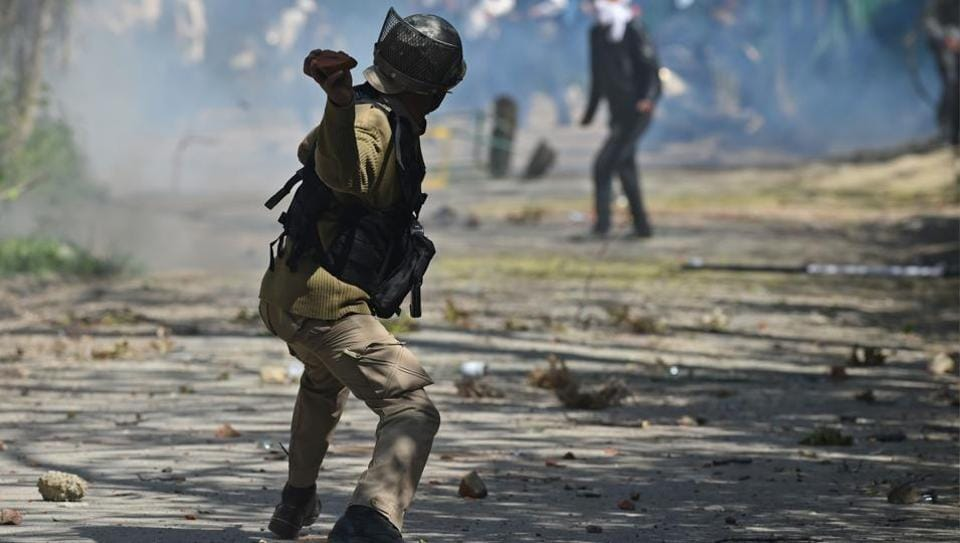 A security personnel throws a stone towards protesters during clashes near a college in central Srinagar's Lal Chowk.