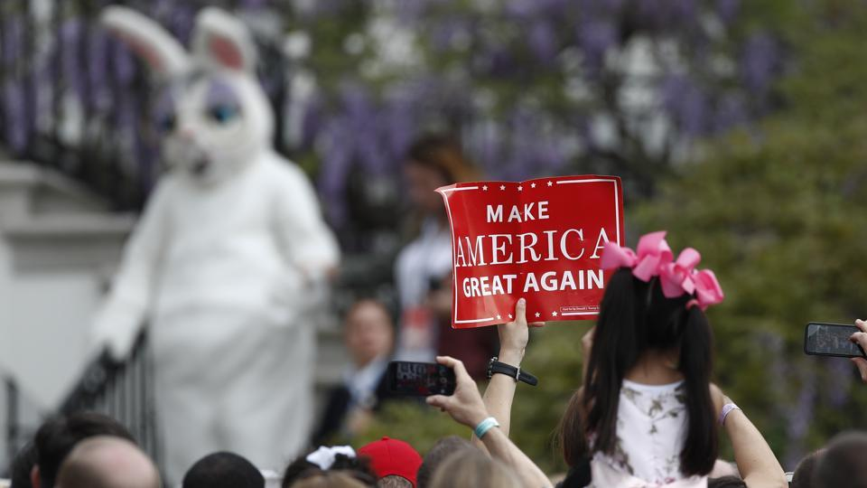 A person holds up a 'make America great again' sign on the South Lawn of the White House in Washington on Easter.