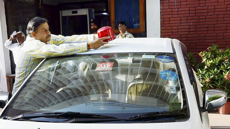 Driver of Union minister Vijay Goel removing the red beacon from the minister's car.