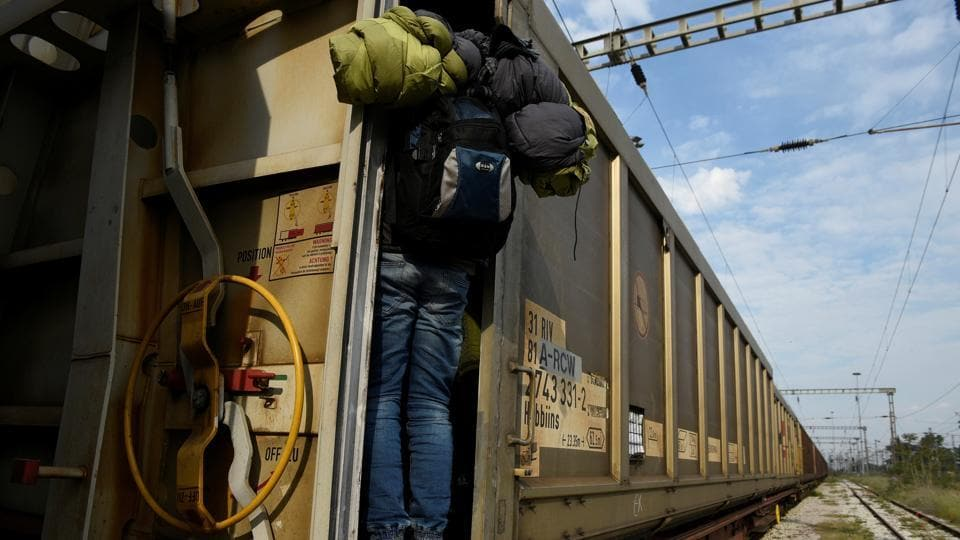 A migrant jumps on a freight train in an effort to cross the Greek-Macedonian border without documents, in the northern city of Thessaloniki, Greece. (Alexandros Avramidis  /Reuters)