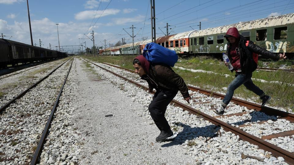 Habib (L), 22, from Algeria and a fellow migrant run to jump on a freight train in an effort to cross the border. (Alexandros Avramidis  /Reuters)