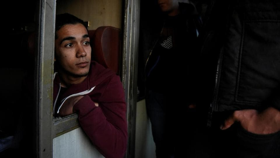 Habib, 22, from Algeria is seen with his friends on an abandoned railway wagon used as a shelter.On April 6, Habib and his friends jumped on a freight train in an effort to cross the Greek-Macedonian border without documents. They were arrested in Macedonia and returned back to Greece. (Alexandros Avramidis  /Reuters)