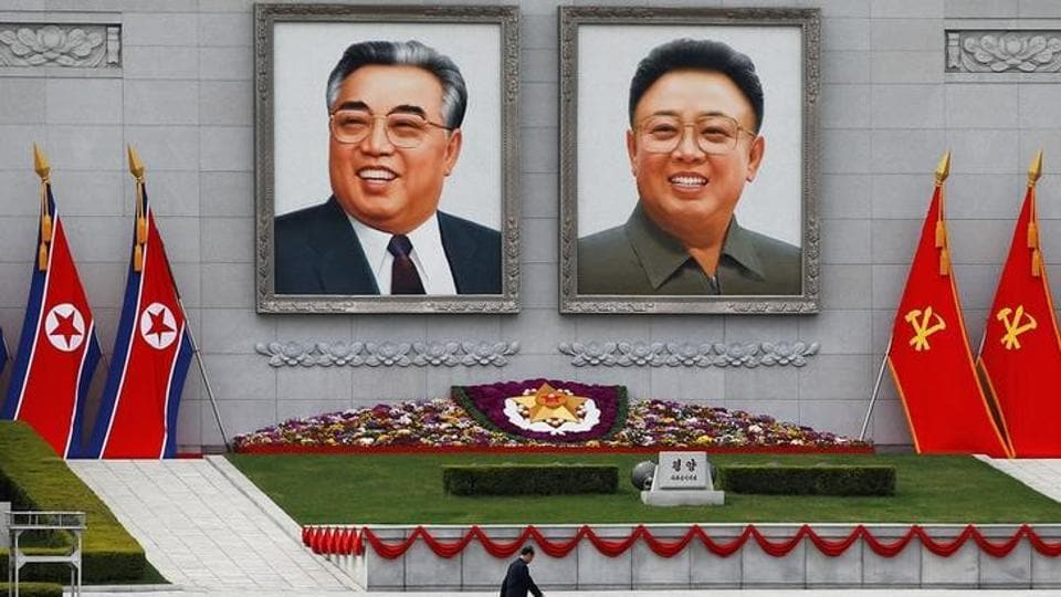 A man walks in front of portraits of North Korea founder Kim Il Sung and late leader Kim Jong Il in central Pyongyang.