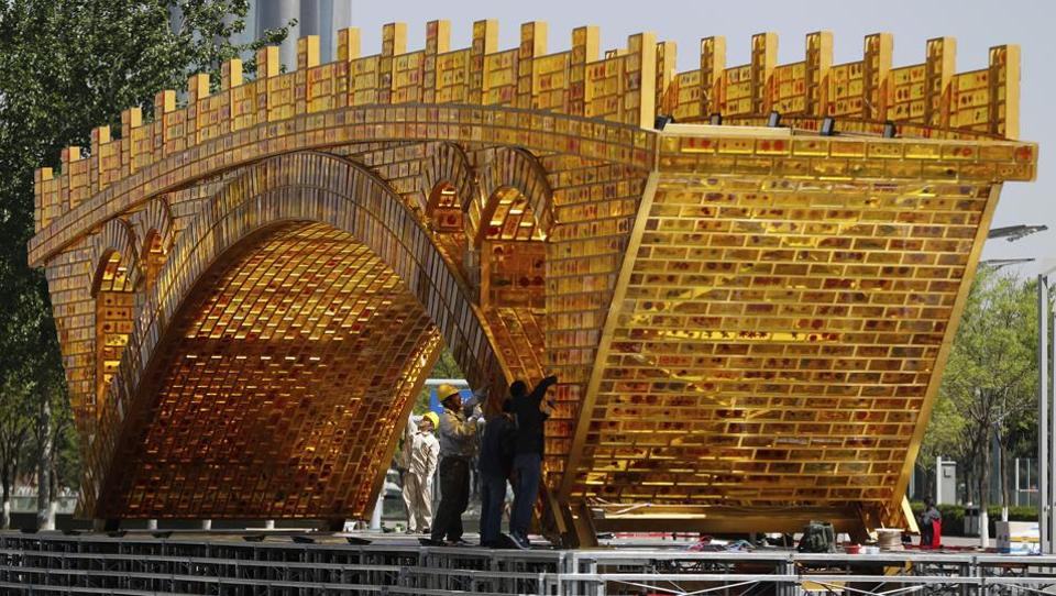 Workers install wires on a 'Golden Bridge of Silk Road' structure on a platform outside the National Convention Center, the venue which will hold the Belt and Road Forum for International Cooperation, in Beijing, April 18.