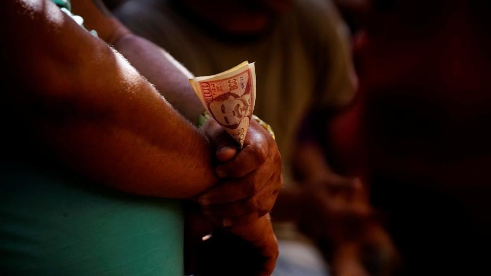 A cockfighting enthusiast holds money during a fight at the arena. (Alexandre Meneghini  / Reuters)