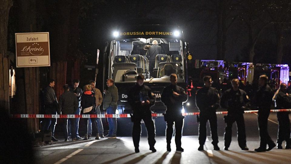 Police officers stand on April 11 in front of Dortmund's damaged team bus after explosions which injured two people before the Champions League quarterfinal soccer match between Borussia Dortmund and AS Monaco in Dortmund, western Germany.