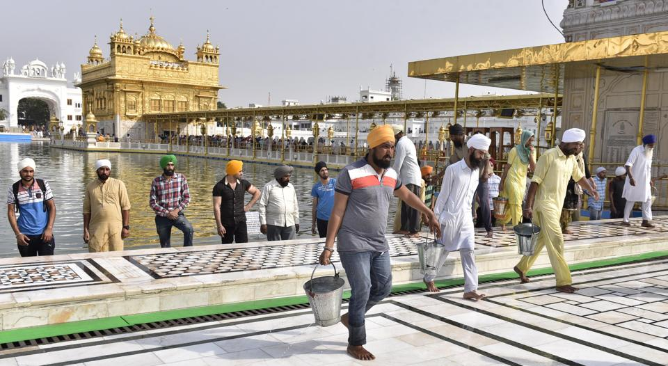 SGPC workers and devotees roll out mats and cool the floor with water from the sacred sarovar (pond) in the parikarma (circumambulation) of the Golden Temple as the summer is already close to its peak in Amritsar on Friday, April 21. (Gurpreet Singh/HT)