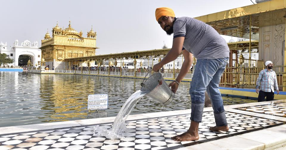 SGPC workers and devotees roll out mats and cool the floor in the parikarma (circumambulation) of the Golden Temple as the summer is already close to its peak in Amritsar on Friday, April 21. (Gurpreet Singh/HT)