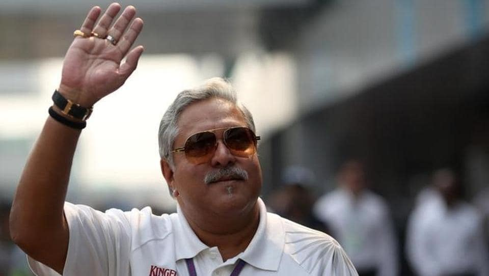 Vijay Mallya waves in the paddock during a practice session of the Indian F1 Grand Prix at the Buddh International Circuit in Greater Noida, on the outskirts of New Delhi.