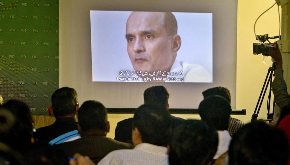 In this March 29, 2016 photo, journalists look at an image of Indian naval officer Kulbhushan Jadhav, who was arrested in March 2016, during a press conference by Pakistan's army spokesman and the Information Minister, in Islamabad.
