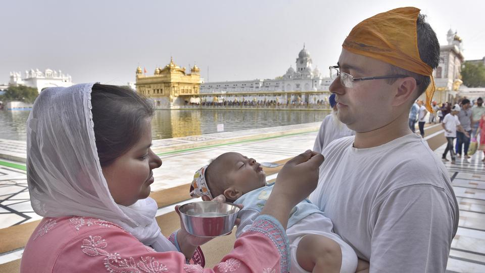 A couple gives water to an infant in the parikarma (circumambulation) of the Golden Temple in Amritsar on Friday, April 21. (Gurpreet Singh/HT)