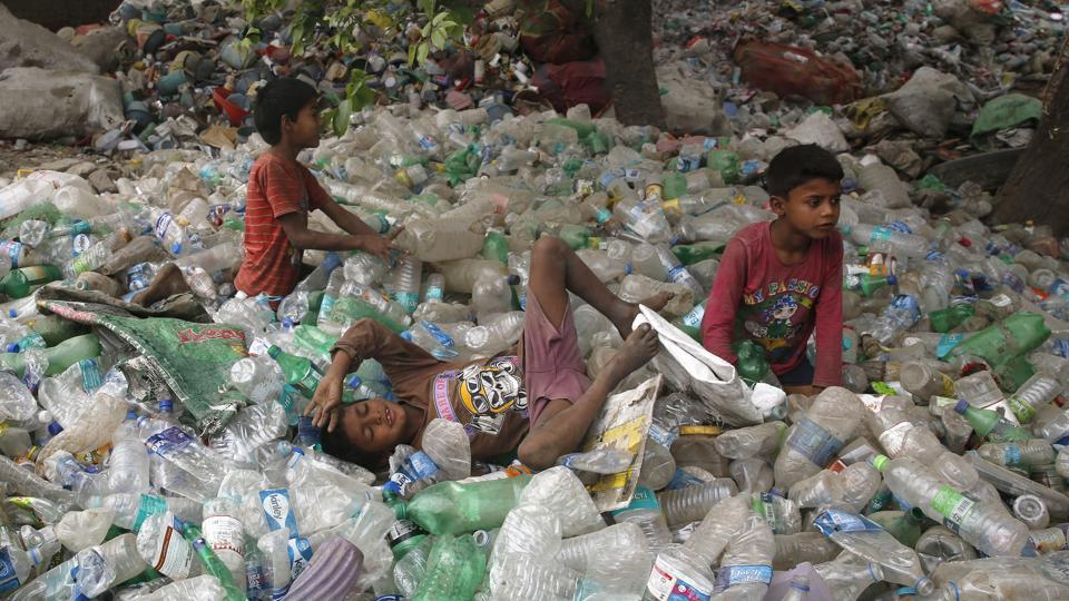 Children rest on plastic bottles after playing on Earth Day in Allahabad, India. (Rajesh Kumar Singh/AP)