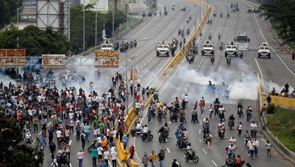 Demonstrators run away from tear gas during clashes with police while rallying against Venezuela's President Nicolas Maduro in Caracas, Venezuela on April 20.
