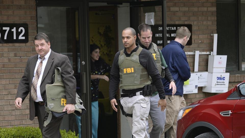 FBI agents leave the office of Dr Fakhruddin Attar at the Burhani Clinic in Livonia, Michigan on Friday.