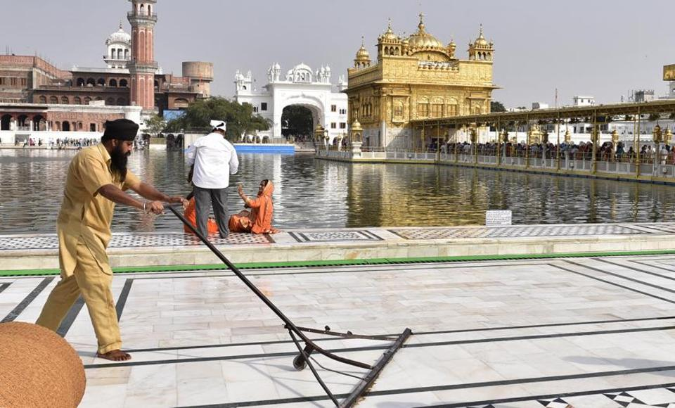 SGPC workers and devotees cool the floor in the parikarma (circumambulation) of the Golden Temple as the summer is already close to its peak in Amritsar on Friday, April 21. (Gurpreet Singh/HT)