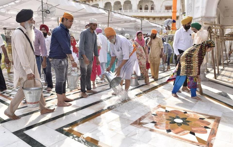 SGPC workers and devotees roll out mats and cool the floor with water and wipers in the parikarma (circumambulation) of the Golden Temple as the summer is already close to its peak in Amritsar on Friday, April 21. (Gurpreet Singh/HT)