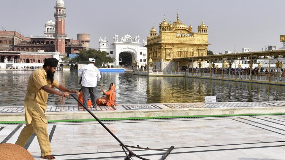 SGPC workers and devotees cool the floor in the parikarma (circumambulation) of the Golden Temple as the summer is already close to its peak in Amritsar on Friday, April 21.