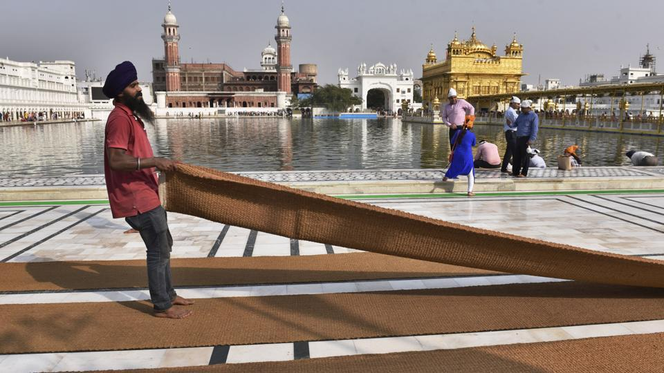 SGPC workers and devotees roll out mats and cool the floor with water and wipers in the parikarma (circumambulation) of the Golden Temple as the summer is already close to its peak in Amritsar. (Gurpreet Singh/HT)
