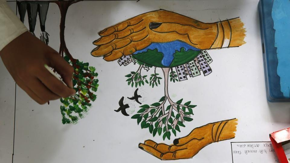 A school child draws a tree promoting conservation of the planet on world Earth Day at the Chandra Shekhar Azad Park in Allahabad. (Rajesh Kumar Singh/AP)