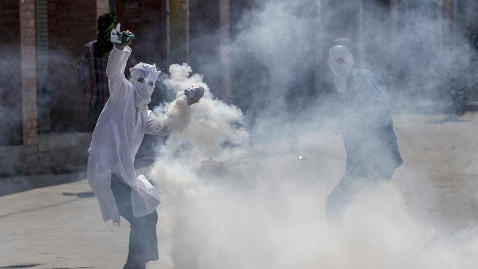 A masked Kashmiri protester throws an exploded tear gas shell back at Indian police during a protest in Srinagar on April 21.