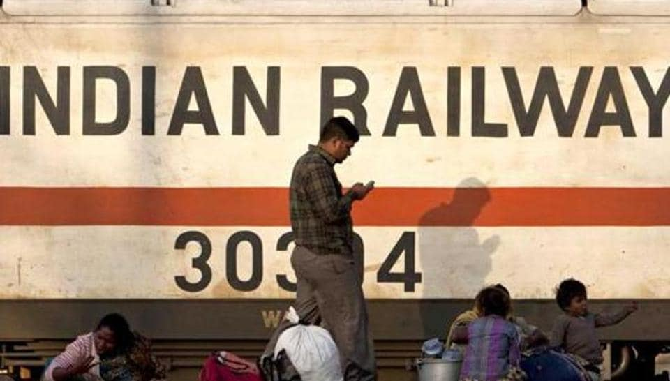 A train engine moves past waiting travellers at a railway station in New Delhi. (AFP Photo)