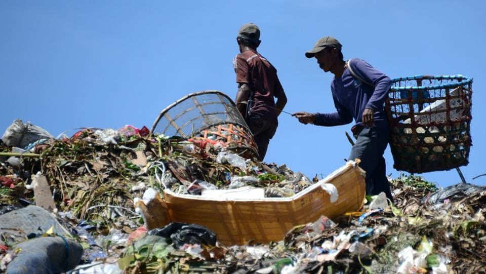 Indonesian scavengers carry items salvaged from a garbage dump in Denpasar. The theme for this year's Earth Day, which is marked on April 22, is Environmental and Climate Literacy.  (Sonny Tumbelaka/AFP)