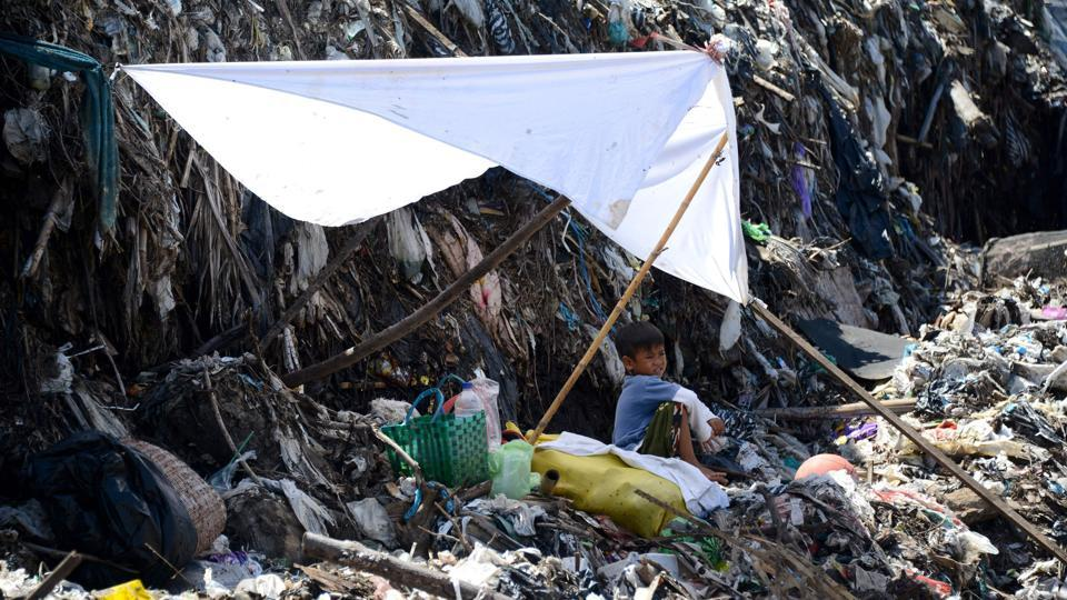 A boy rests in the shade while waiting for his father to salvage items from a garbage dump in Denpasar. (Sonny Tumbelaka/AFP)