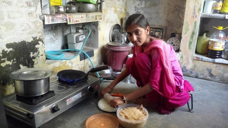 A resident preparing meal for her family using biogas that is supplied through pipes at village Lambra in Hoshiarpur on Friday.