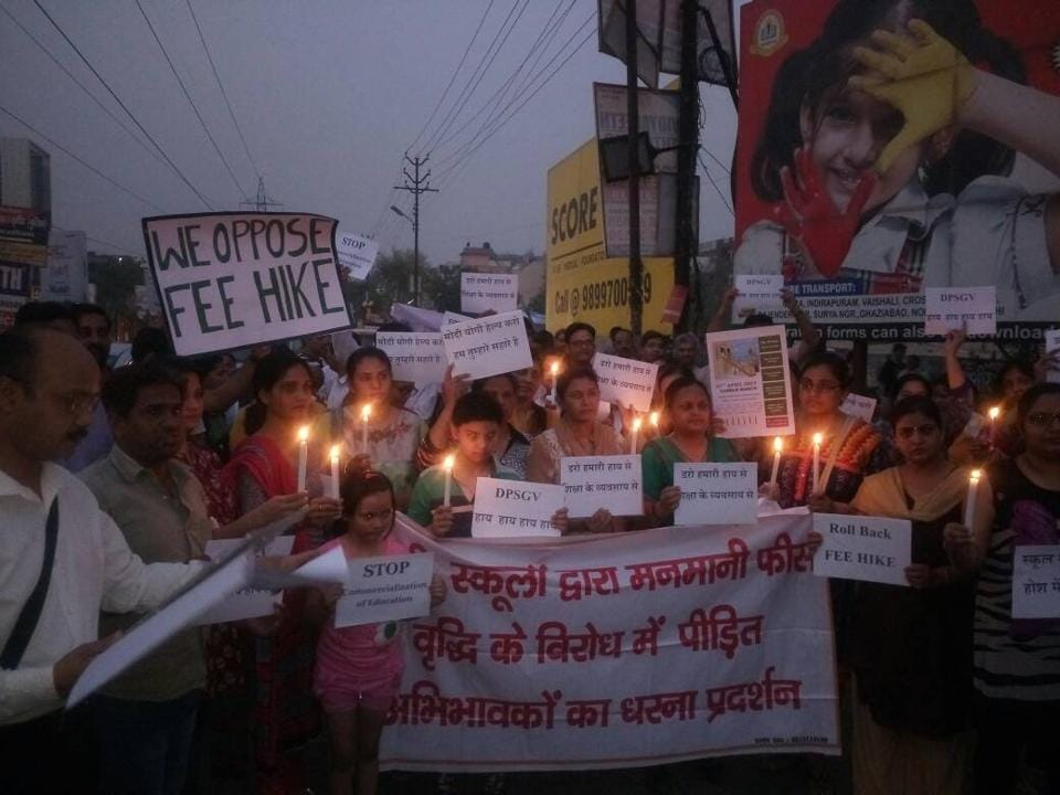Parents take out a candle light march to protest against the fee hike by Noida's private schools.