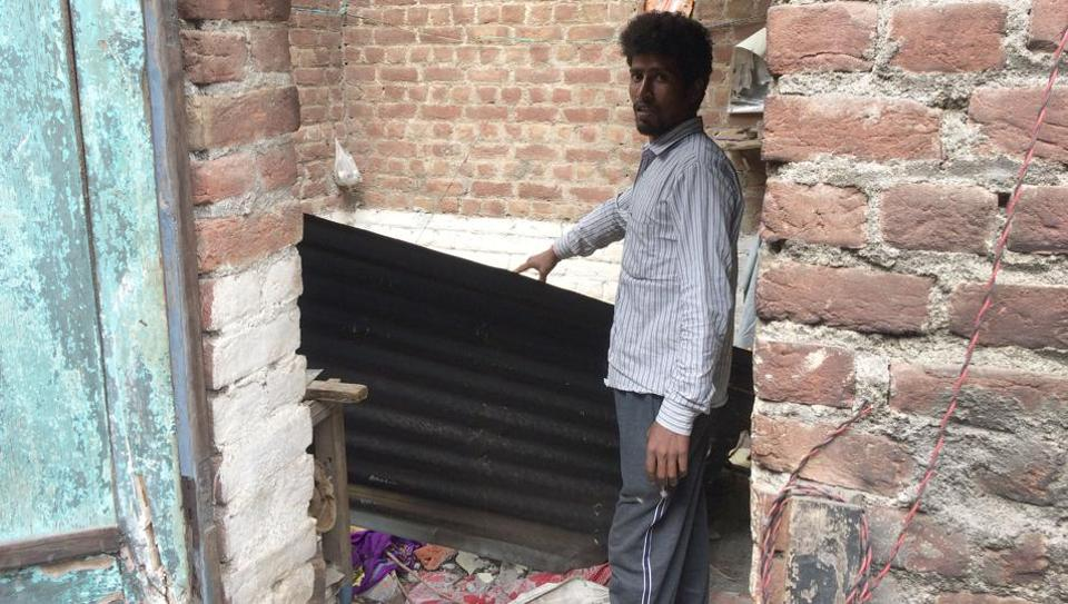 A man showing collapsed roof of the house at Abrol Nagar in Pathankot on Saturday.