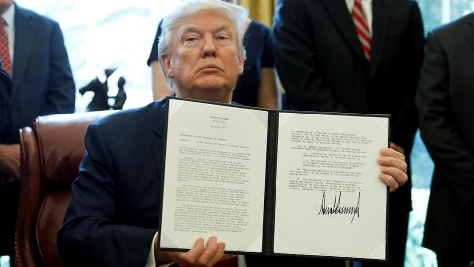 U.S. President Donald Trump holds up a directive ordering an investigation into the impact of foreign steel on the American economy after signing it in the Oval Office of the White House in Washington on April 20, 2017.  (Aaron P. Bernstein/REUTERS)