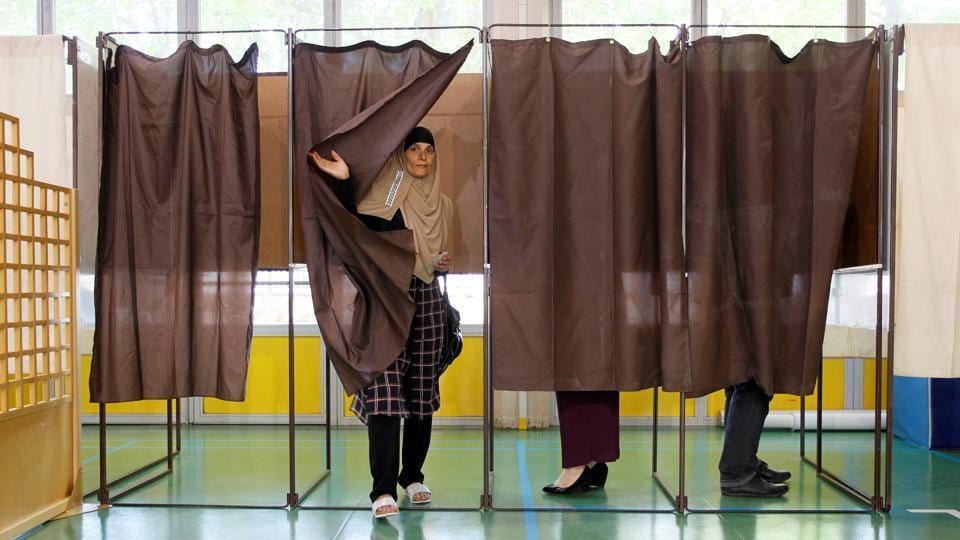 A woman leaves a polling booth in Vaulx-en-Velin near Lyon after voting in the first round of the 2017 French presidential election on Sunday.