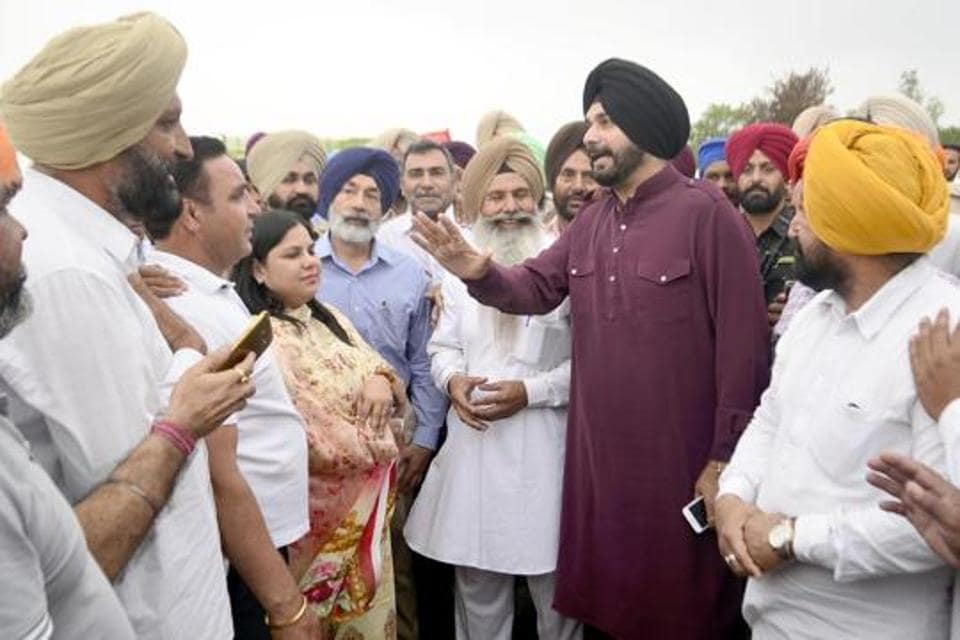 Punjab local bodies minister Navjot Singh Sidhu meeting farmers of village Othianto whose wheat crop was destroyed in fire, on Saturday.