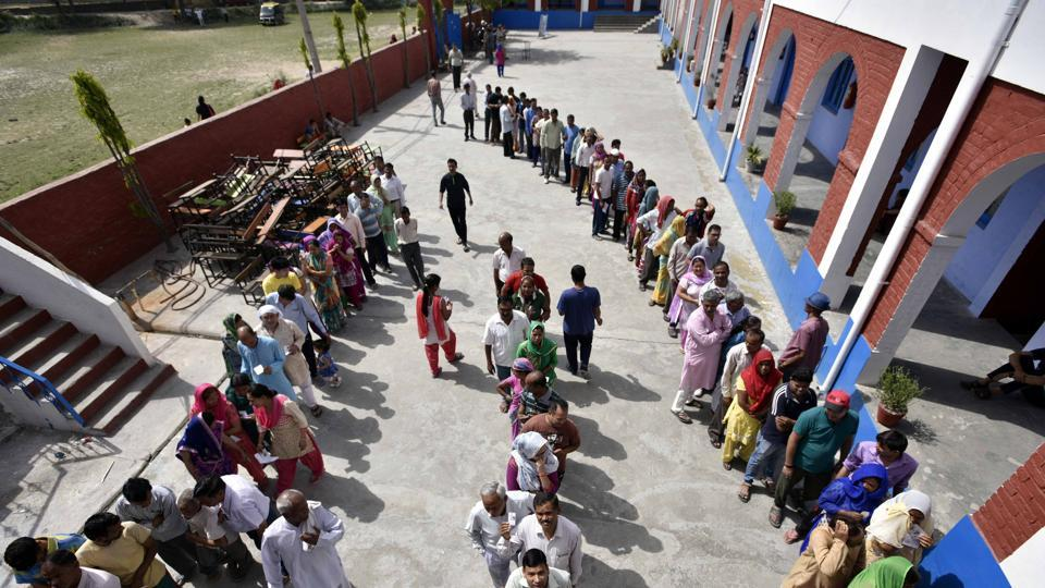 People waiting in queue at a polling booth to cast their vote in Delhi on Sunday.