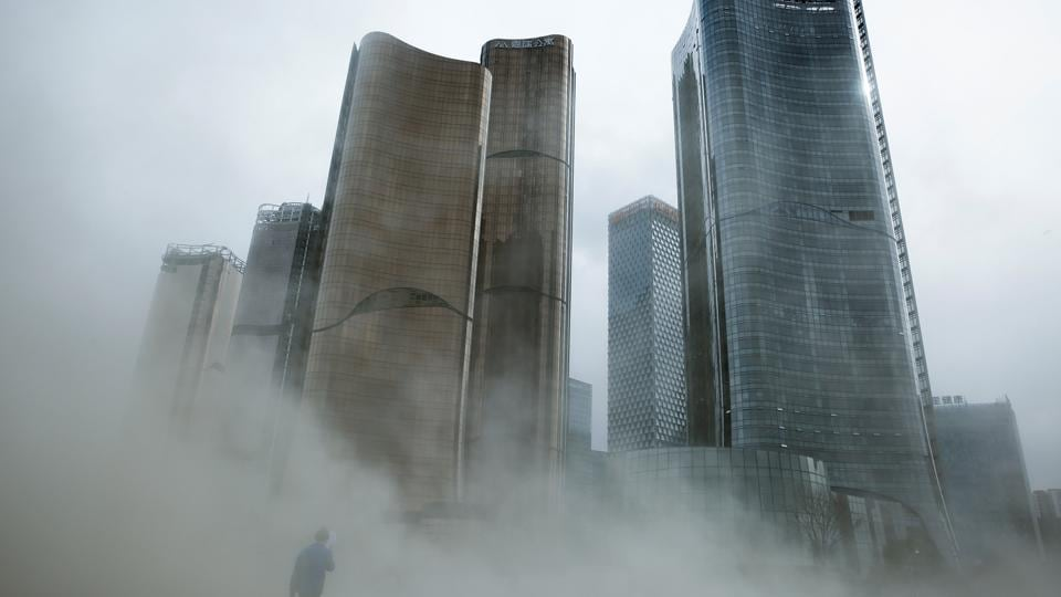A man walks through a cloud of dust whipped up by wind at the construction site near newly erected office skyscrapers in Beijing on April 20, 2017.  (Thomas Peter/REUTERS)