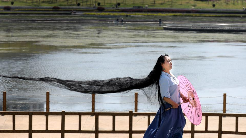 A woman with long hair poses for pictures in Weihai, Shandong province in China on April 22,. (REUTERS)