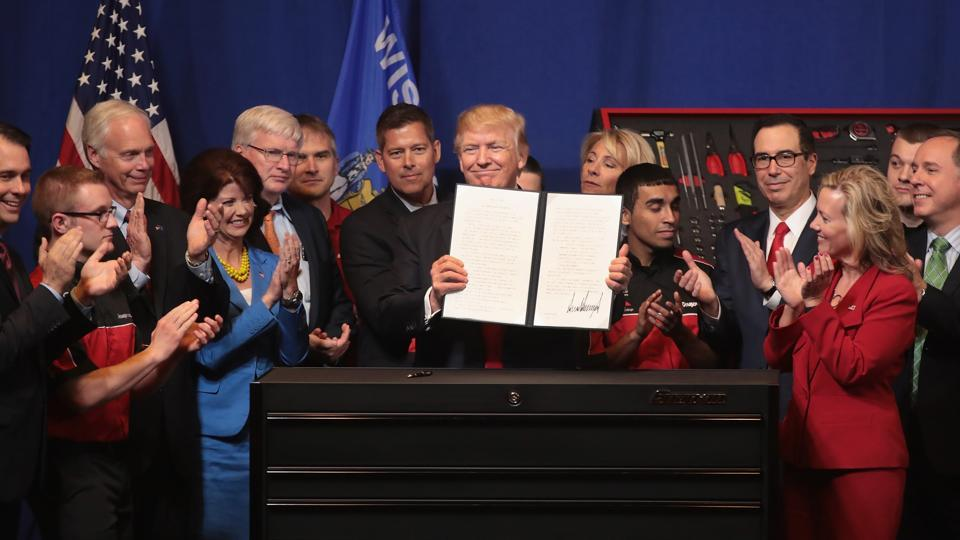 President Donald Trump signs an executive order to try to bring jobs back to American workers and revamp the H-1B visa guest worker programme during a visit to the headquarters of tool manufacturer Snap-On on April 18, 2017 in Kenosha, Wisconsin.