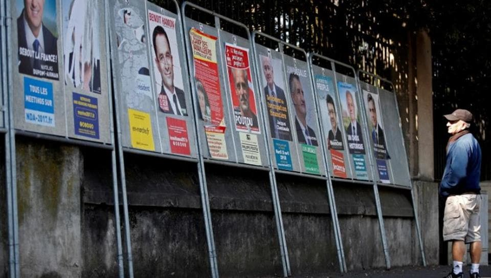 A man looks at campaign posters of the 11th candidates who run in the 2017 French presidential election in Enghien-les-Bains, near Paris, on April 19, 2017.